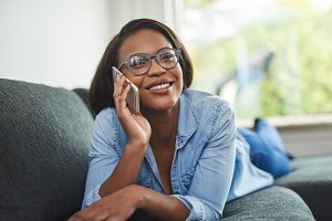 Smiling young African woman talking on a cellphone at home