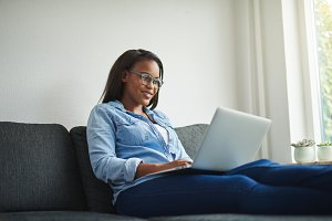Young African woman sitting alone at home using a laptop