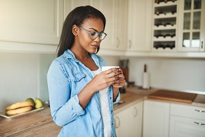 Young African woman drinking a cup of coffee at home