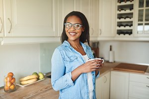 Smiling African woman standing in her kitchen with a coffee