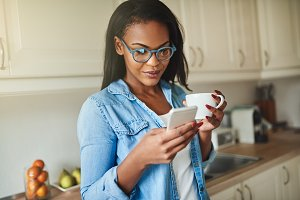 Young African woman drinking coffee and reading text messages