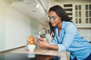 Young African woman drinking coffee and texting on a cellphone