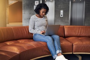 Focused young African university student working online on campus