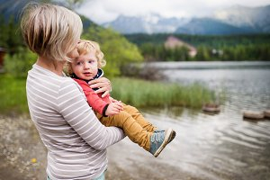 Senior woman with little boy at the lake, summer day.