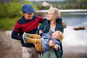 Senior couple with little boy at the lake.