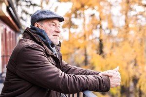 Senior man resting on a terrace in autumn nature.