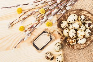 Quail eggs in the bowl and bouquet of dry flowers on the wooden background