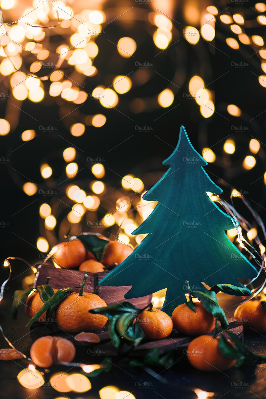 wooden christmas tree with fairy lights and clementines on a dark background festive new year