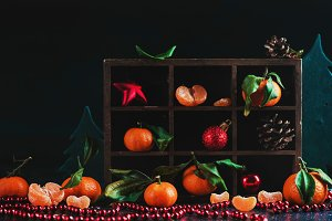 Christmas tangerines in a wooden shadow box on a dark background. Vibrant ripe fruit concept with pine cones, decorations, and garlands. New Year preparations concept.