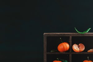 Tangerines in a wooden shadow box on a dark background. Dark food photography with vibrant orange fruit and copy space.