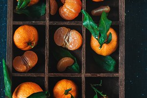 Tangerines in a wooden case on a dark background. An assortment of clementines with green leaves. Dark food photography with vibrant orange fruit and copy space.