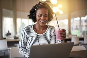 Smiling African college student drinking a smoothie and studying
