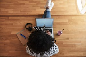 African female university student working online on a campus floor