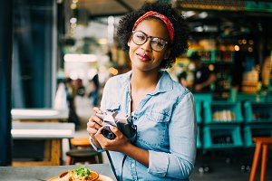 Smiling young woman photographing her food on a cafe counter
