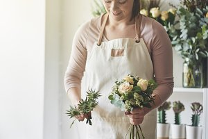 Female florist making a floral arrangement in her flower shop