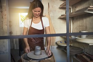 Artisan creatively turning clay on a wheel in her workshop