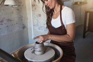 Creative artisan making pottery on a wheel in her studio