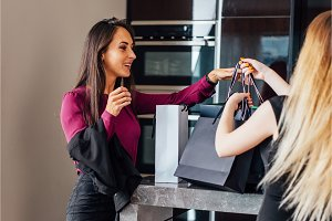 Cheerful elegant girls standing in the stylish interior with luxury shopping bags happy with their purchases