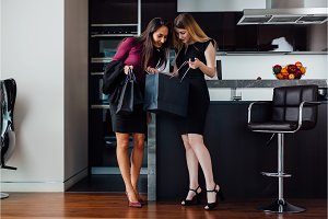 Smiling young women wearing formal elegant clothes looking into shopping bag standing in the modern apartment