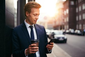Young executive sending texts and drinking coffee in the city