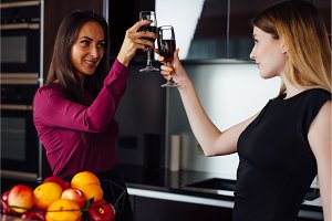 Two successful female friends wearing elegant clothes drinking wine clinking glasses standing in the kitchen