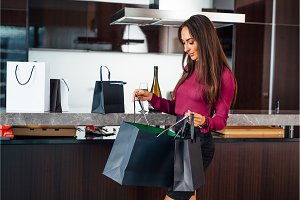 Stylish elegant lady at home after shopping peeping into the bags reviewing her purchases