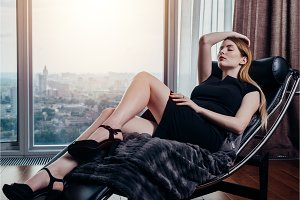 Portrait of female model wearing short black dress and high heels relaxing on chair