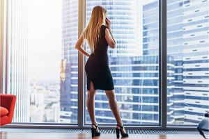 Back view of successful businesswoman having phone conversation looking out the window with cityscape view
