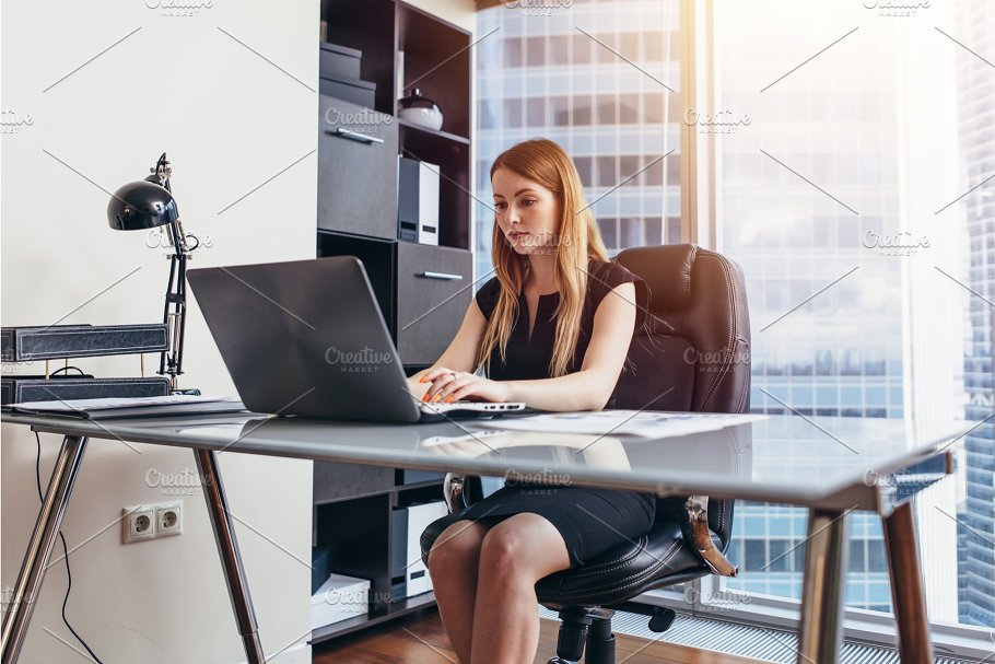 Woman Working On Laptop Sitting At Her Desk In Office Business Photos Creative Market