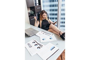 Portrait of relaxed female boss sitting at workplace with feet on table planning her workday writing goals in notebook