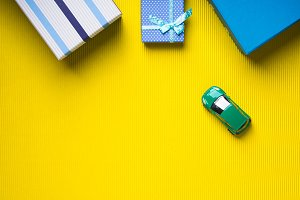 Gift boxes and toy car on yellow background