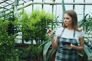 Young woman working in garden center. Attractive girl check and count flowers using tablet computer during work in greenhouse