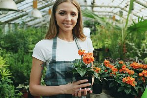 Portrait of Cheerful young woman garden worker in apron smiling and holding flower in hands in greenhouse