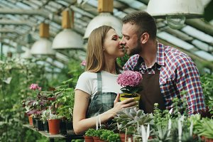 Happy young florist couple in apron working in greenhouse. Attractive man embrace and kiss his wife holding flower and smile together into camera