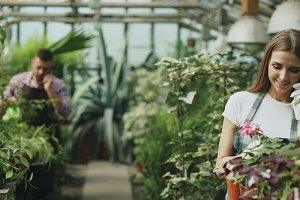Young cheerful woman in apron and gloves talking phone while gardening plants and loosen ground in flower in greenhouse