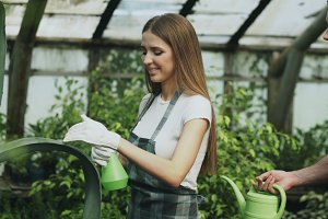 Happy young florist couple in apron have fun while working in greenhouse.