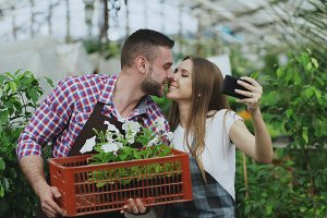 Cheerful loving couple gardeners taking selfie picture on smartphone camera and kissing while working in greenhouse