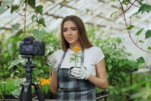 Young smiling blogger woman florist in apron talking and recording video blog for her online vlog about gardening