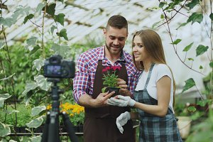 Young smiling blogger couple gardeners in apron holding flower talking and recording video blog for online vlog about gardening