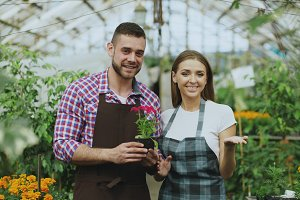 Pan shot of young smiling blogger couple gardeners in apron holding flower talking and recording video blog for online vlog about gardening