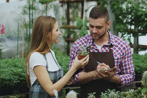 Young couple florists work in garden center. Attractive man cheking flowers and woman using tablet computer during working in greenhouse