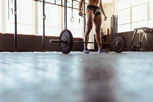 Fit woman with barbell in gym