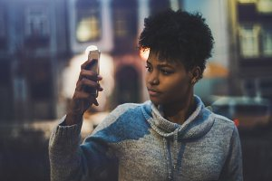 Black girl photographing at night