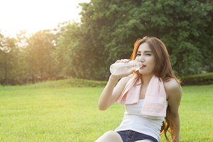 Woman drinking water and sit