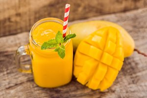Healthy ripe Yellow Mango Smoothie, Mango fruit and mango cubes on the wooden table, concept healthy food