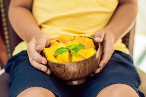 Little cute boy eating mango on the terrace