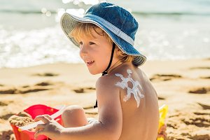 The sun drawing sunscreen ,suntan lotion on baby boy back. Caucasian child is sitting with plastic container of sunscreen and toys on sunny beach. Close up, outdoor