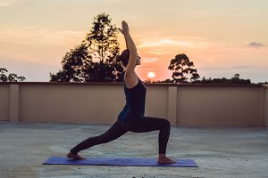 Young athletic woman practicing yoga on the roof at sunset, silhouette