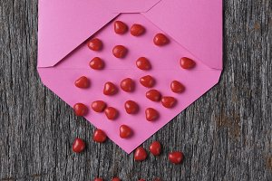 Pink envelope on wood surface with r