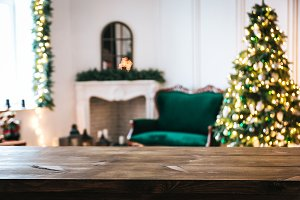 Christmas holiday background with empty rustic table and the bokeh of the living room with the Christmas tree, sofa and fireplace on the second plan